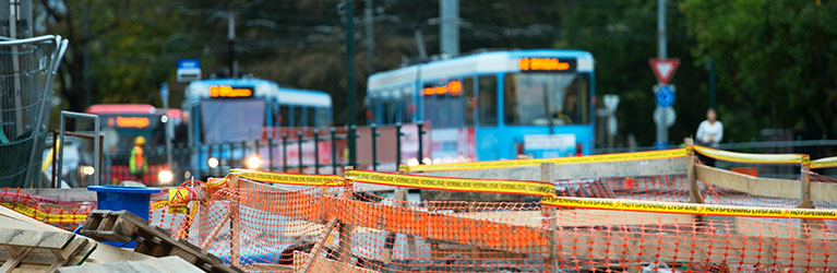 Construction work area with buses and trams in the background. Photo.